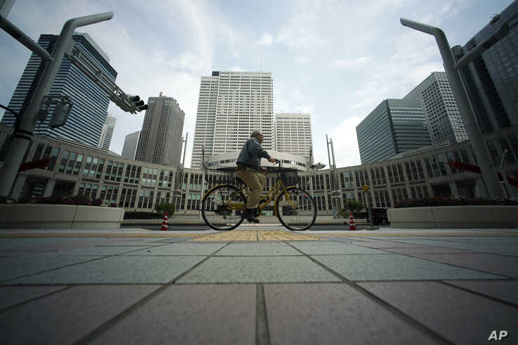 A man with a protective mask rides a bicycle at usually crowded street at lunch time at Tokyo's Shinjuku district Friday, April…