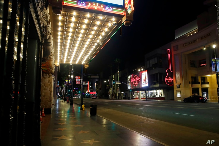 An empty Hollywood Boulevard is seen under the neon lights of El Capitan Theatre, top left, Thursday, April 2, 2020, in Los…