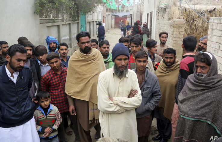 In this Tuesday, Feb. 4, 2020 photo, Pakistani villagers gather outside the home of student Muhimman, who was allegedly abused…