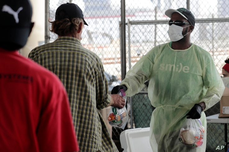 Melvin Armstrong, of the Smile Trust, right, hands out meals and cold drinks to the homeless during the new coronavirus…
