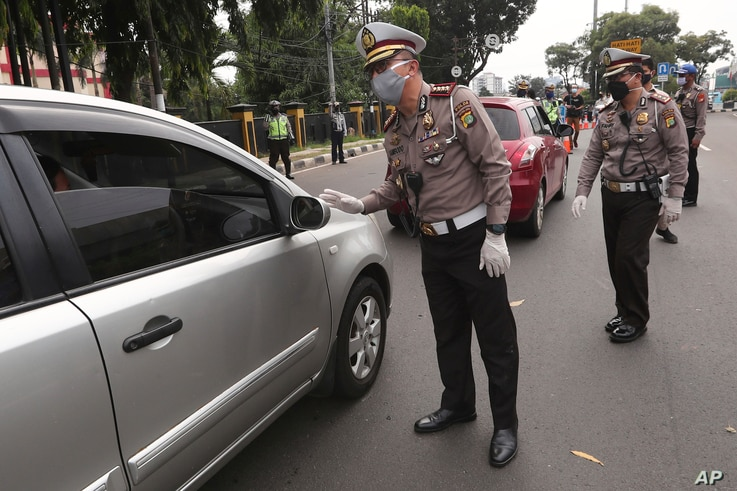 Police officers check the number of people seated inside a car during the imposition of large-scale social restriction, at a…