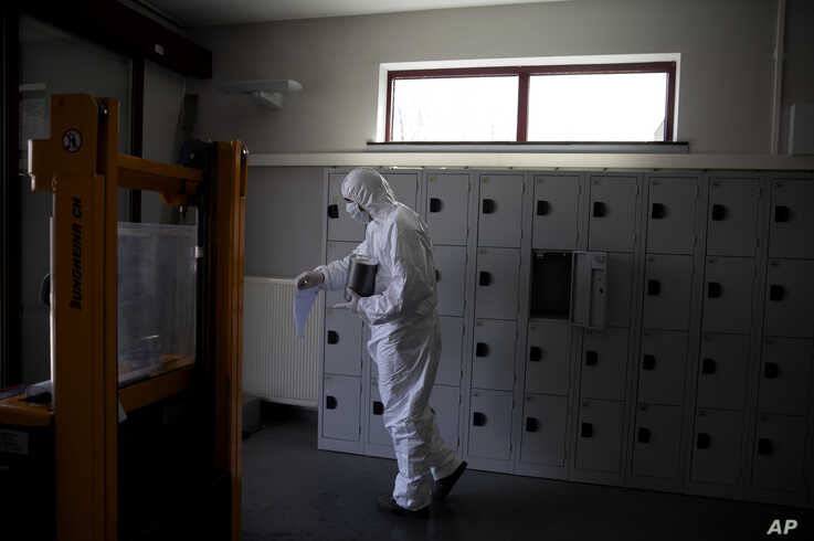 A worker in protective gear carries an urn of ashes of a Covid-19 deceased at the Pontes crematorium and funeral center in…