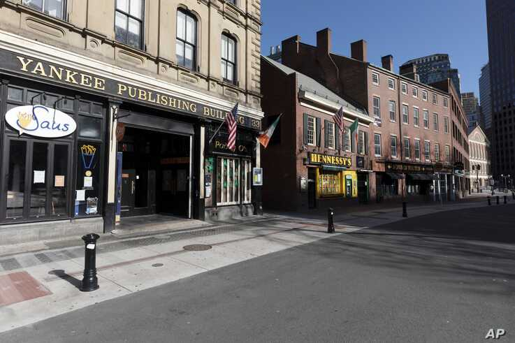 A block of closed restaurants on a deserted street ends at Faneuil Hall, right, Saturday, April 4, 2020, in Boston. The area is…