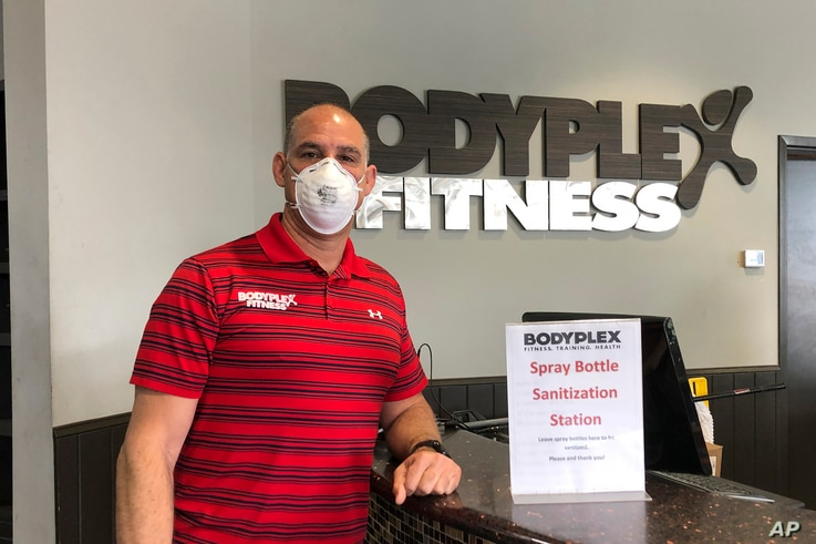 Gym co-owner, Mike Martino, poses for a portrait with a mask to protect against coronavirus, at Bodyplex Fitness Adventure on…