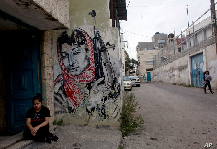 A Palestinian girl sits at the entrance of her family's house at Aida Refugee camp ahead of the funeral procession of 13 year…