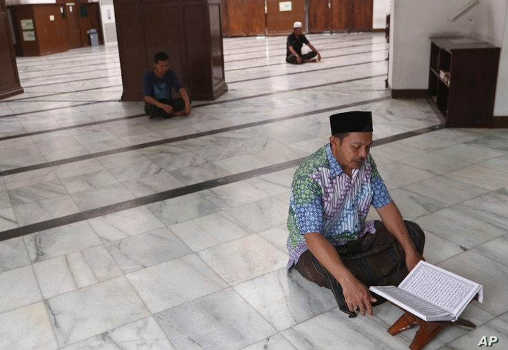 A man reads the holy book of Quran at an empty mosque in Jakarta, Indonesia, Friday, April 10, 2020. Mosques usually filled for…