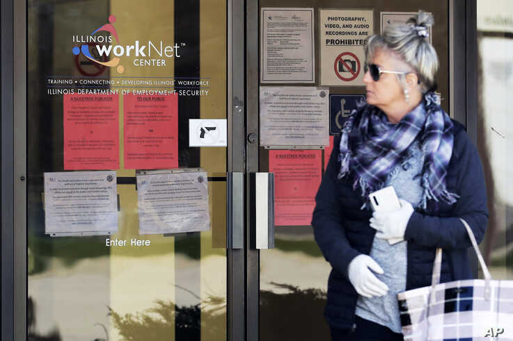 A woman looks to get information about job application in front of IDES (Illinois Department of Employment Security) WorkNet…