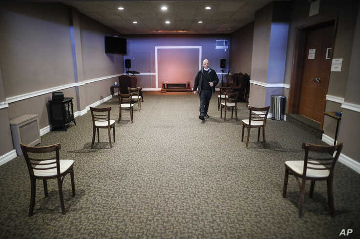 Pat Marmo, owner of Daniel J. Schaefer Funeral Home, walks through a viewing room set up to respect social distancing, Thursday…