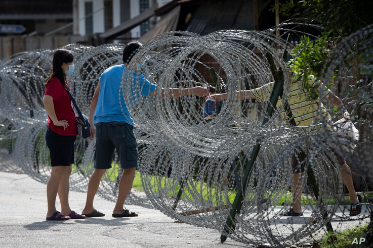 A man shares supplies through barbed wire fence in the coronavirus lockdown area of Selayang Baru, in Kuala Lumpur, Malaysia,…
