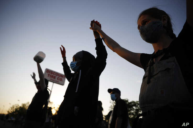 Demonstrators join hands Thursday, May 28, 2020, in St. Paul, Minn. Protests over the death of George Floyd, a black man who…