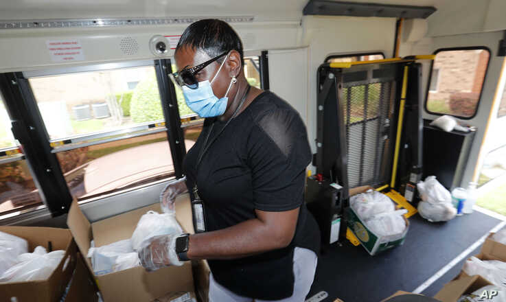 Amid concerns of the spread of COVID-19, school lunch worker Brenda Alexander wears a mask as she prepares to distribute meals…