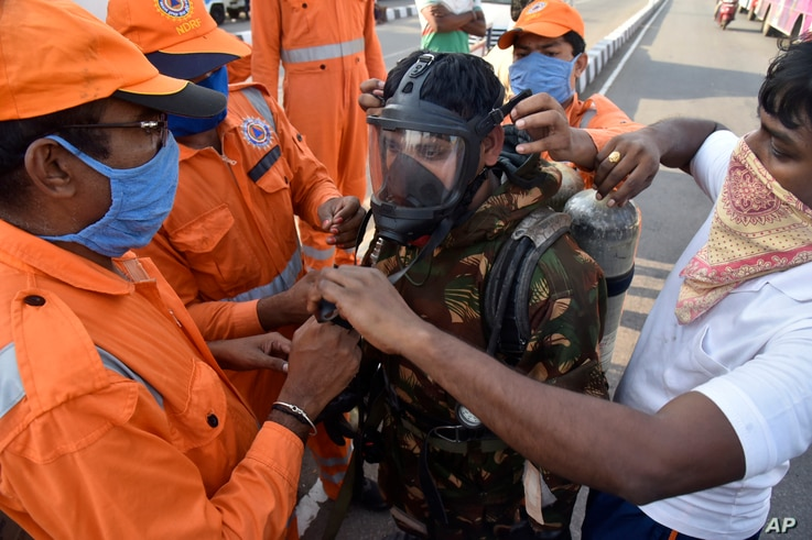 A National Disaster Response Force (NDRF) soldier is fitted with gear before he proceeds to the area from where chemical gas…