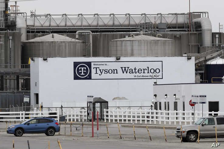 Vehicles sit in a near empty parking lot outside the Tyson Foods plant, Friday, May 1, 2020, in Waterloo, Iowa. (AP Photo…