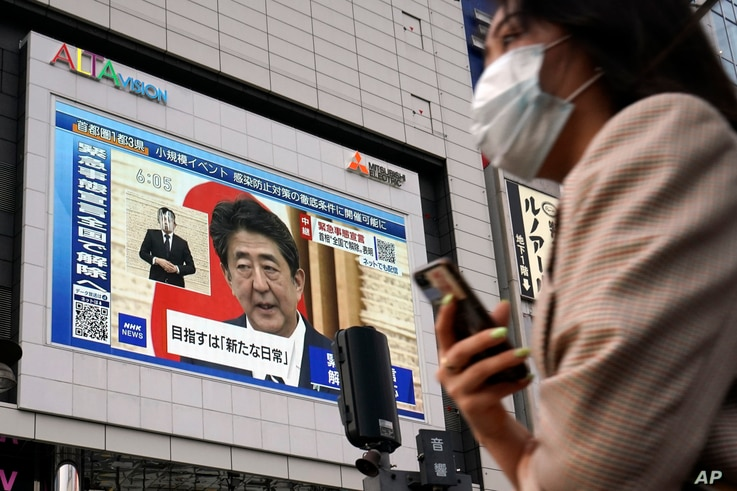 A public screen shows Japanese Prime Minister Shinzo Abe speaking at a press conference Monday, May 25, 2020, in Tokyo. Abe…