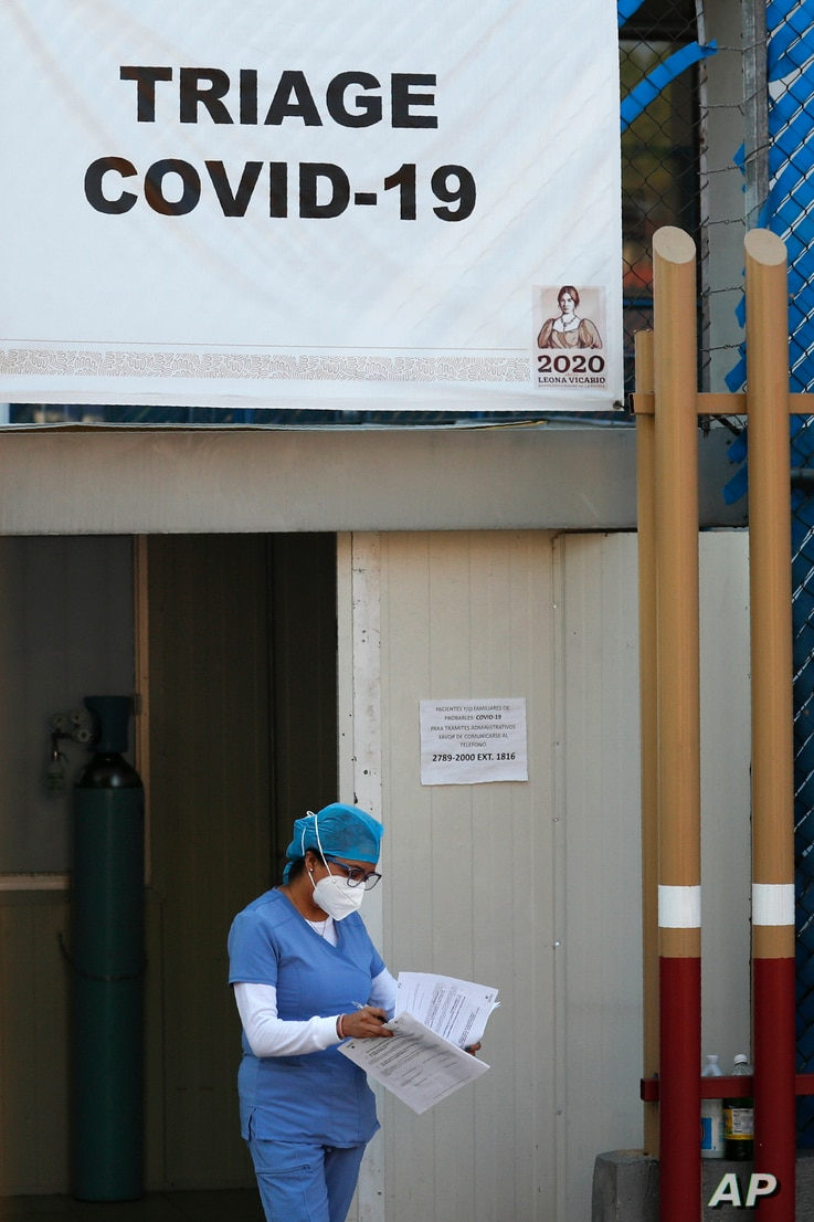 A medical worker from the COVID-19 triage carries paperwork at the Mexico General Hospital, in Mexico City, Tuesday, May 12,…