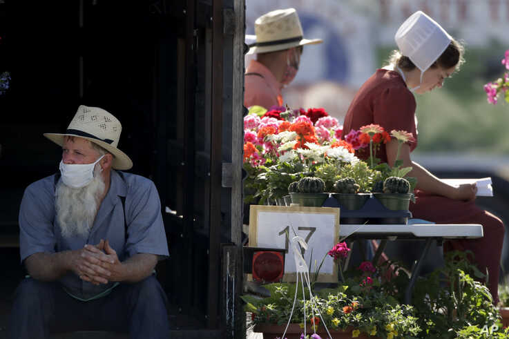 Vendors wait for customers at a drive-thru farmers market Saturday, May 2, 2020, in Overland Park, Kan. The market has moved…
