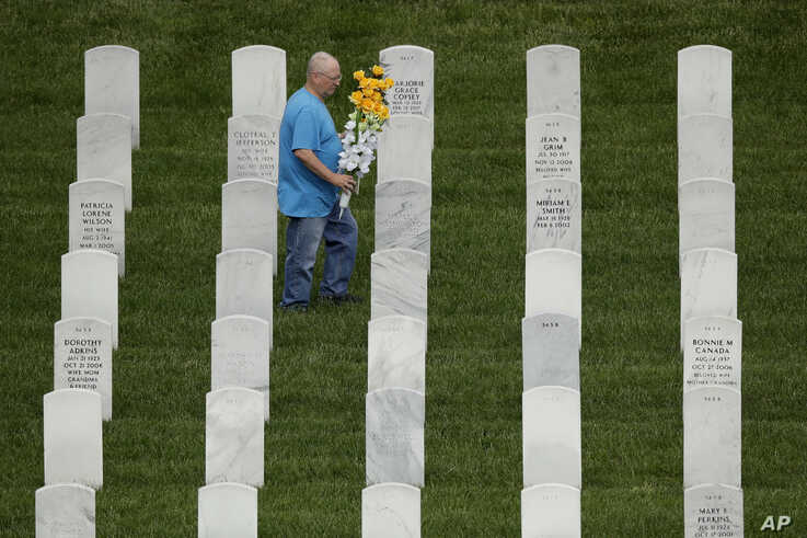 A man looks for a grave while visiting Leavenworth National Cemetery Saturday, May 23, 2020 in Leavenworth, Kan. Several people…