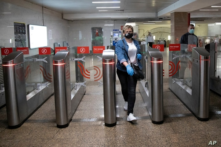 A woman wearing face mask and gloves to protect against coronavirus, observes social distancing guidelines as she passes…