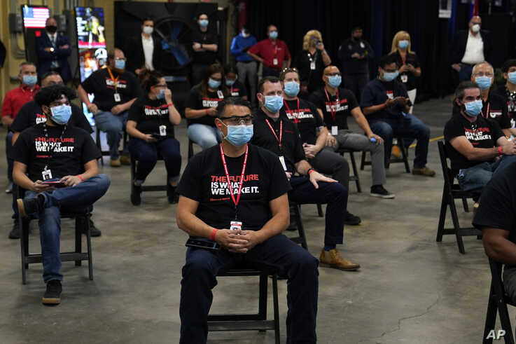 Employees wait to hear President Donald Trump speak after a tour of a Honeywell International plant that manufactures personal…