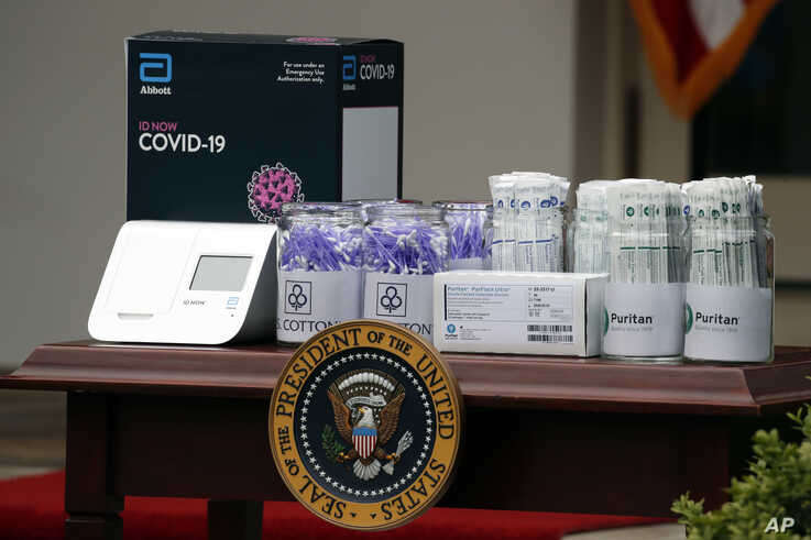 Materials for COVD-19 testing from Abbott Laboratories, U.S. Cotton, and Puritan are displayed as President Donald Trump speaks…