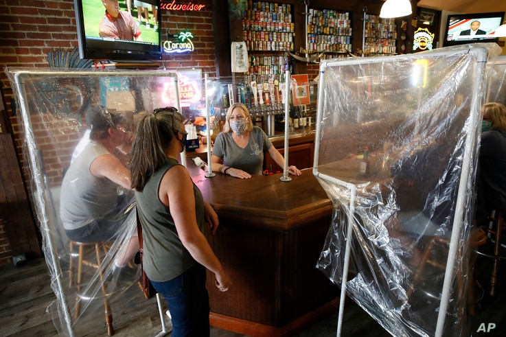 Sheila Kelly, owner of Powell's Steamer Co. & Pub, center, stands behind makeshift barriers as she helps patrons at her…