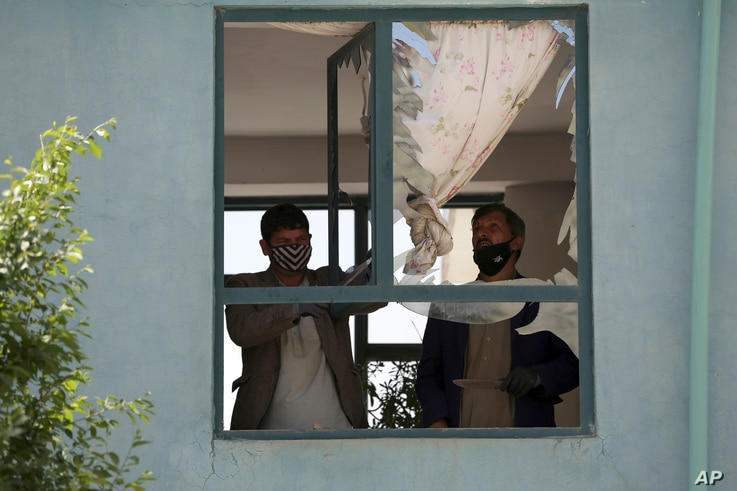 Afghans clear glass from a broken window of a house after a suicide bomb attack, on the southern outskirts of Kabul,…