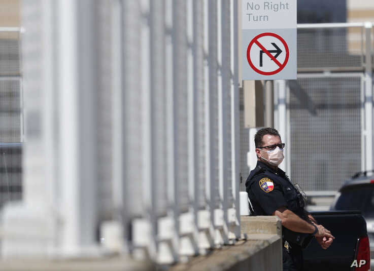 Amid concerns of the spread of COVID-19, a police officer wears a mask in Dallas, Wednesday, May 6, 2020. (AP Photo/LM Otero)