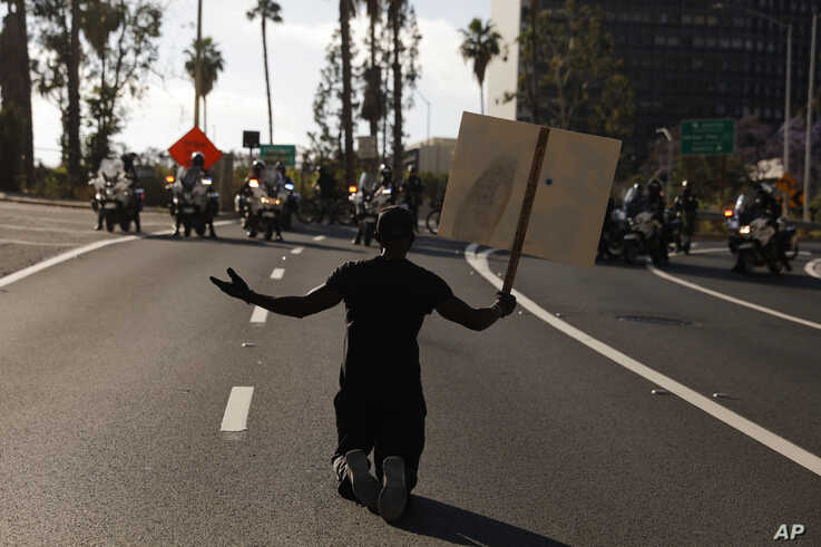 "A man kneels on the street in front of police officers while chanting ""I can't breathe"" during a protest over the death of…"