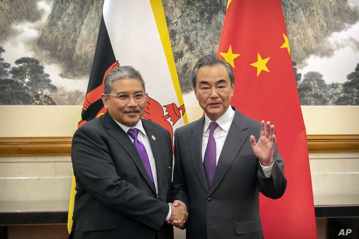 Chinese Foreign Minister Wang Yi, right, shakes hands with Brunei's Second Minister of Foreign Affairs and Trade Erywan Yusof…