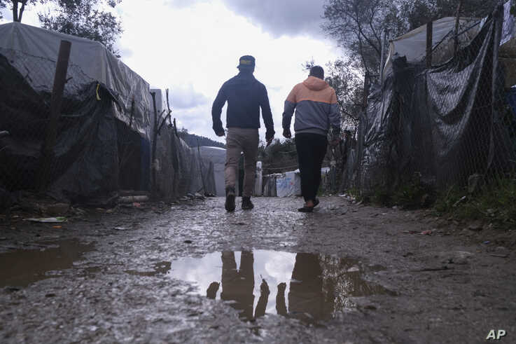 Migrants walk past makeshift tents outside the perimeter of the overcrowded Moria refugee camp on the northeastern Aegean…