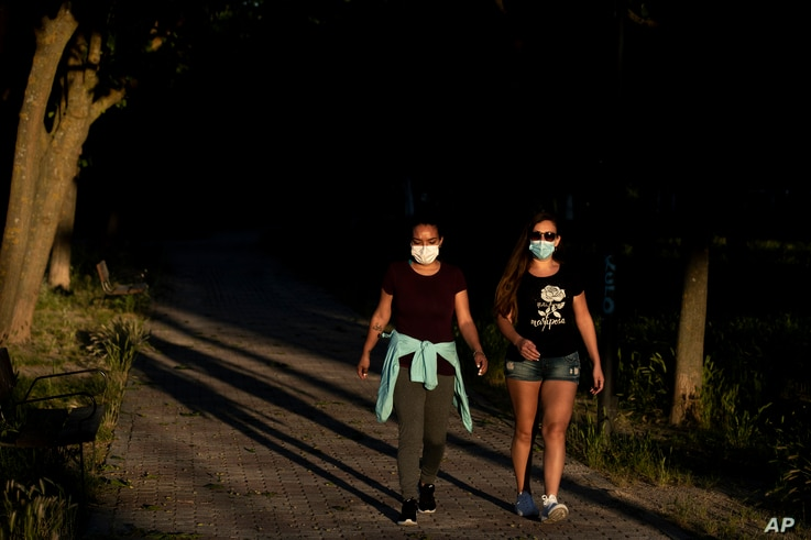 People wearing face masks to combat the spread of coronavirus walk in a public park in Madrid, Spain, Wednesday, May 6, 2020…