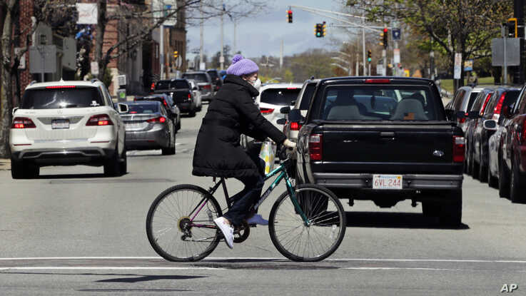 A woman wears a protective mask and gloves, due to the COVID-19 virus outbreak, as she bicycles through busy traffic in…