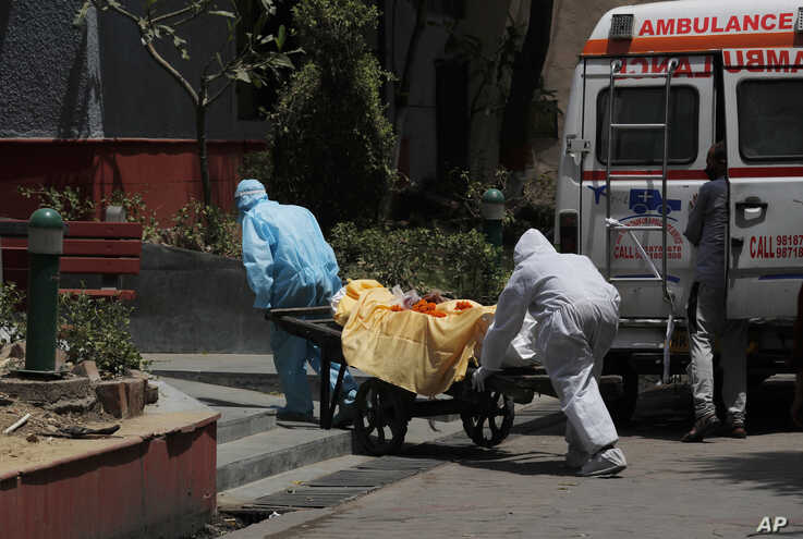 Health workers in personal protective suits ferry the body of a man who died of Covid 19 on a handcart for cremation in New…