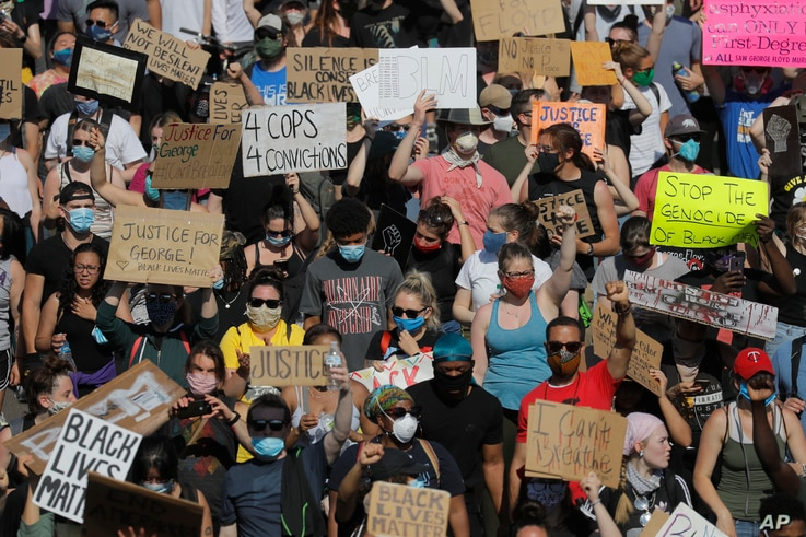 Demonstrators march on pavement, Sunday, May 31, 2020, in Minneapolis. Protests continued following the death of George Floyd,…