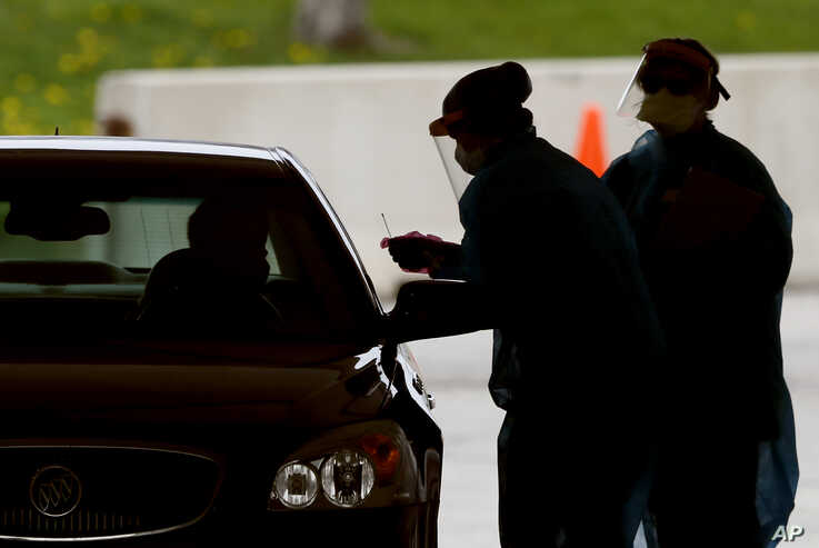In this Friday, May 1, 2020, photo, medical workers test a local resident at a drive-thru COVID-19 testing site in Waterloo,…