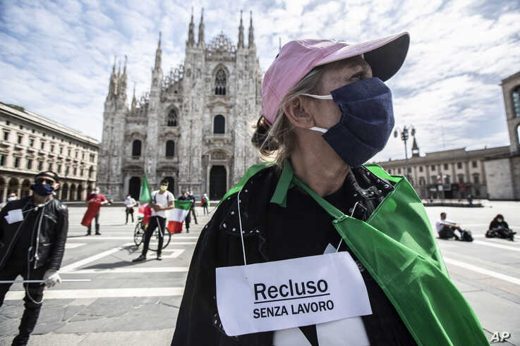 People stage a protest against government and for work rights in front of the Duomo gothic cathedral, in Milan, Italy, Monday,…