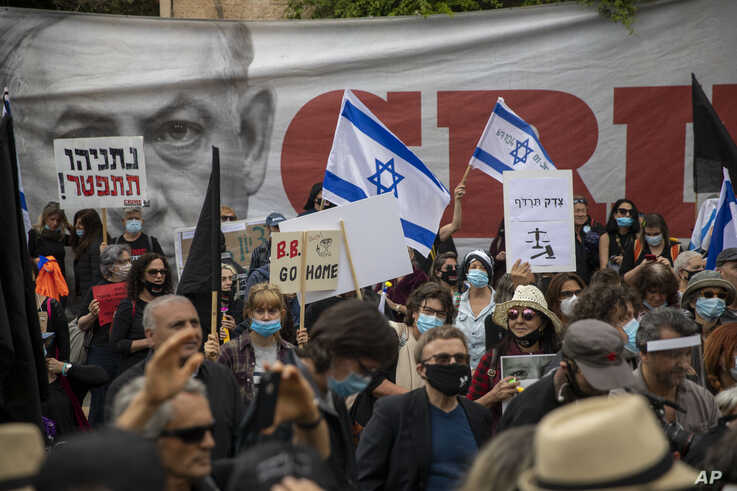 Protesters against Israel's Prime Minister Benjamin Netanyahu wave flags and banners outside his residence in Jerusalem, Sunday…