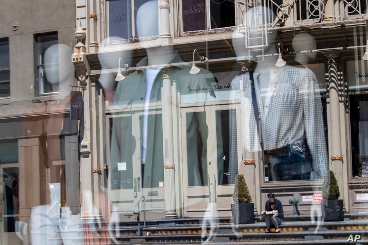 A woman sitting on a stoop reading a book in the sun is seen reflected by a closed clothing store's window on West Broadway,…