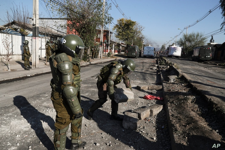 Police clear a barricade during clashes demanding food aid from the government during the COVID-19 lockdown, at a poor…