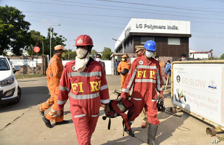 Firefighters walk with oxygen cylinders outside LG Polymers plant, the site of a chemical gas leak, in Vishakhapatnam, India,…