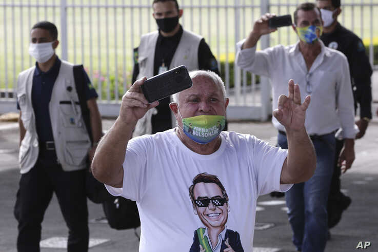 A supporter of Brazil's President Jair Bolsonaro, wearing a face mask amid the new coronavirus pandemic and a T-shirt covered…
