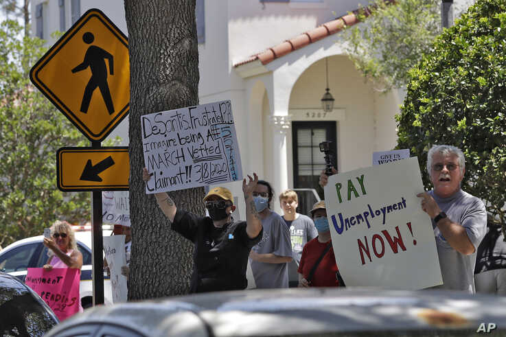 Protestors wave signs at Florida Gov. Ron DeSantis as he and Vice President Mike Pence visit the Westminster Baldwin Park…