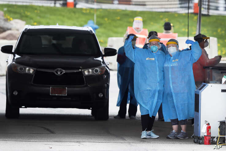 In this Friday, May 1, 2020, photo, medical workers flex their muscles as they pose for a photo at a drive-thru COVID-19…