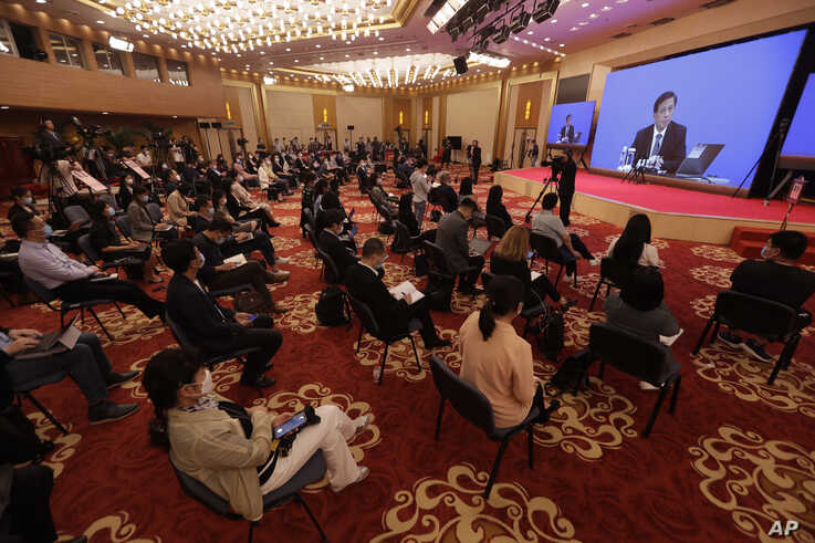 Journalists attend a news conference by Zhang Yesui, a spokesman for the National People's Congress, broadcast remotely to the…
