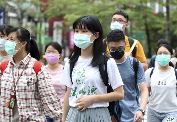 People wearing face masks to protect against the spread of the coronavirus travel around Taipei, Taiwan, Monday, May 18, 2020. …