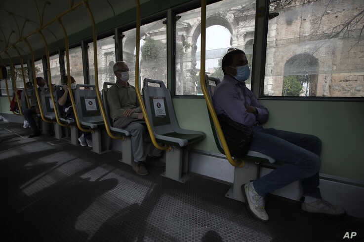 People wearing a sanitary mask and respecting social distancing to protect against COVID-19 sit on a tramcar, in Rome,…