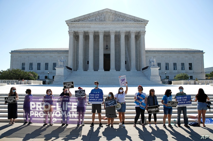 Anti-abortion protesters wait outside the Supreme Court for a decision, Monday, June 29, 2020 in Washington on the Louisiana…
