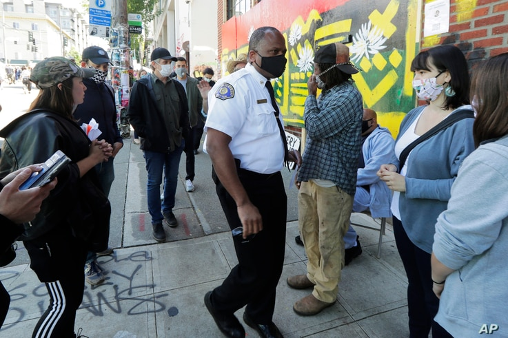 Seattle Fire Chief Harold Scoggins, center, arrives to meet with residents and community leaders, Sunday, June 14, 2020, inside…