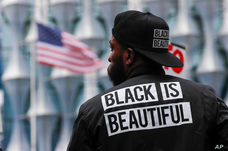 A protester stands in front of the US embassy during the Black Lives Matter protest rally in London, Sunday, June 7, 2020, in…