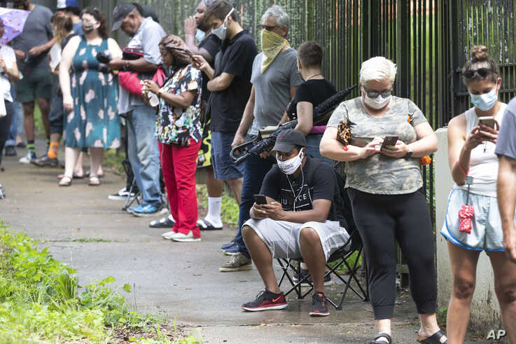 Steven Posey checks his phone as he waits in line to vote, Tuesday, June 9, 2020, at Central Park in Atlanta. Voters reported…